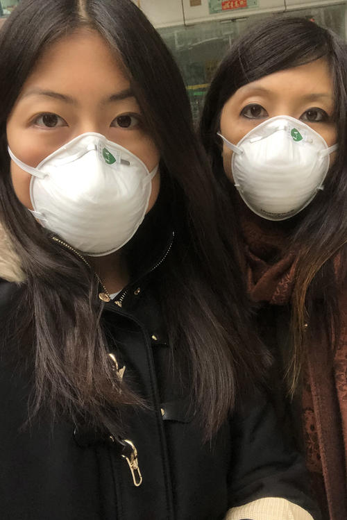 Masks on at all times: Vivi Feng (left) and her sister in Shanghai. Vivi Feng is now back in Germany.