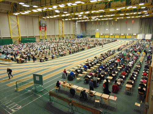 Written tests in the gym: In Canada written tests are taken together, regardless of subject and school year. In this gym there was space for 2880 students in the 36 rows of 80 tables.