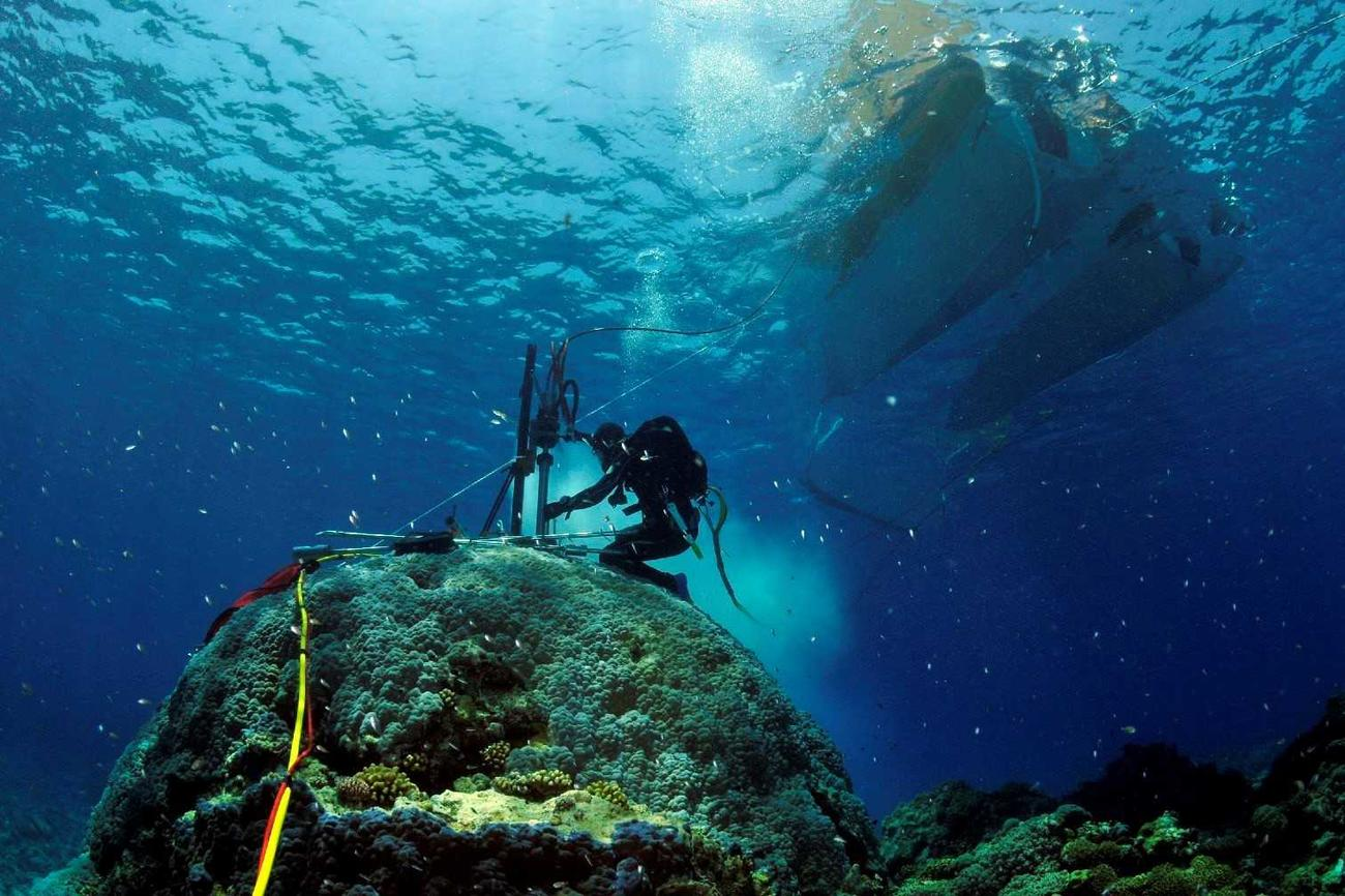 Scientists drilling coral on the Rowley Shoals, a group of three coral reefs protruding from the water similar to atoll coral reefs off the northwestern coast of Australia.