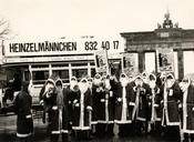 Many students from Freie Universität are hired through Heinzelmännchen to work as Santa Claus. Here, a group of them is promoting the job in front of Brandenburg Gate. The photo was taken around 1988.