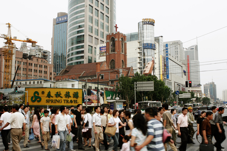 98f0885ea38b64 Menschen überqueren auf einem Zebrastreifen eine Straße am Platz des Volkes  in Shanghai. Im Hintergrund